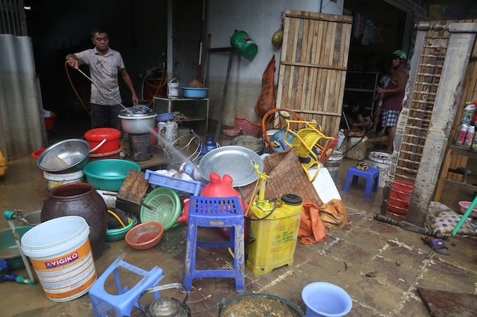 A man using high-pressure water to remove the mud from his household items.Total death in the three provinces Lai Chau, Ha Giang and Lao Cai reached 14 people and 11 are missing as of Monday night. Damage in these provinces has been estimated at VND160 billion ($7 million) thus far.