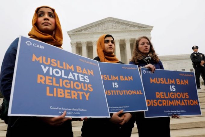 Protesters gather outside the U.S. Supreme Court, while the court justices consider case regarding presidential powers as it weighs the legality of President Donald Trumps latest travel ban targeting people from Muslim-majority countries, in Washington, DC, US. Photo by Reuters