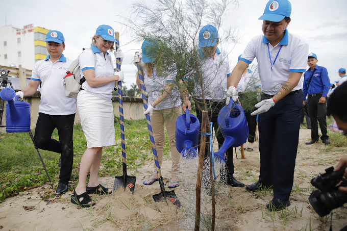 Representatives from the Ministry and GEF are planting a tree to commemorate the event.