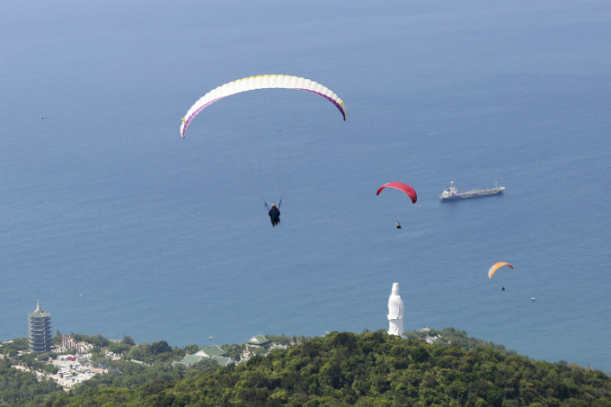 Paragliders are flying on top of Linh Ung pagoda.
