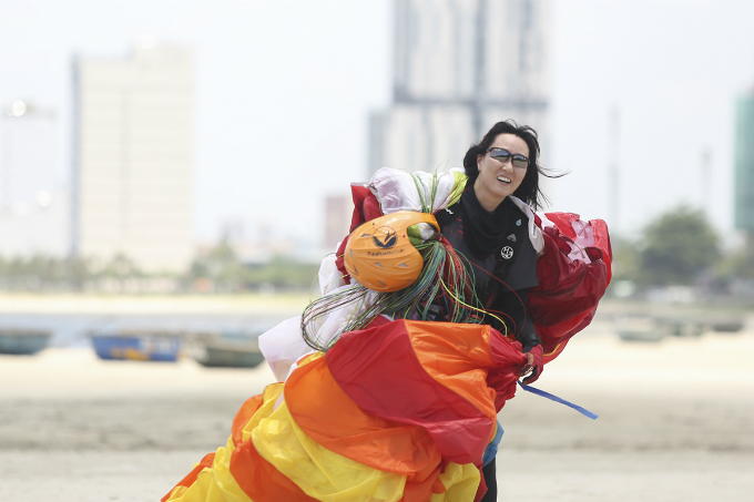 A pilot collected his parachute after a happy landing.