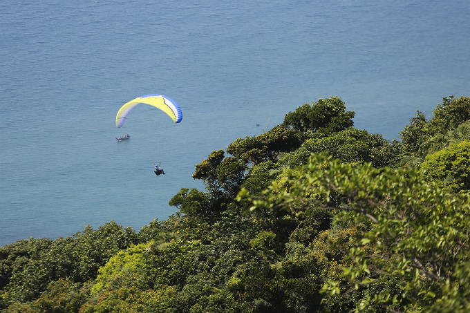 Athletes glide above the deep blue ocean and green forests.