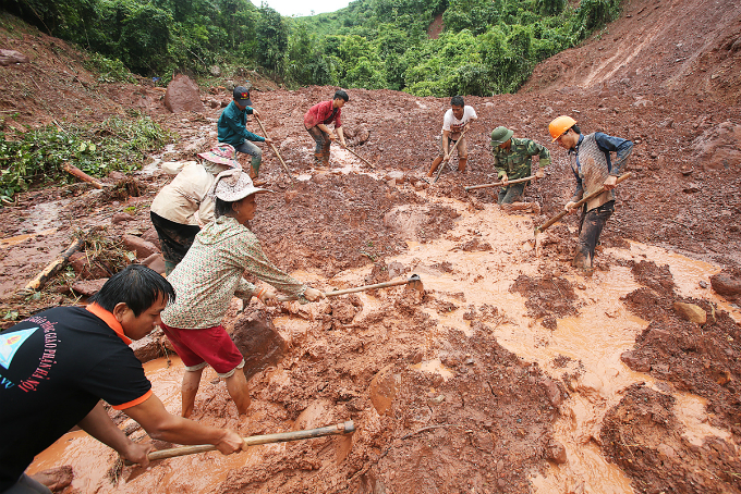 Villagers dig the ground in a remote valley of Lai Chau Province to look  for four victims that have gone missing for three days after landslide  completely destroyed their village in the blink of an eye.