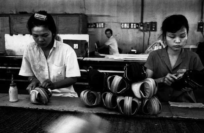 Two women pair sandals in a factory.
