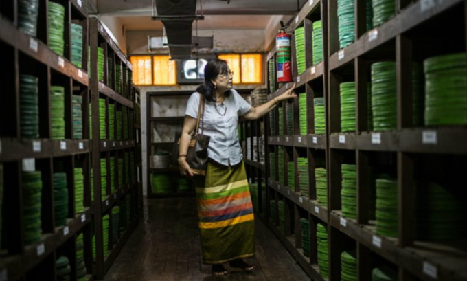 This picture taken on May 15, 2018 shows former actress Grace Swe Zin Htaik viewing storage of old films at the state archive building in Yangon. Photo by AFP/Phyo Hein Kyaw