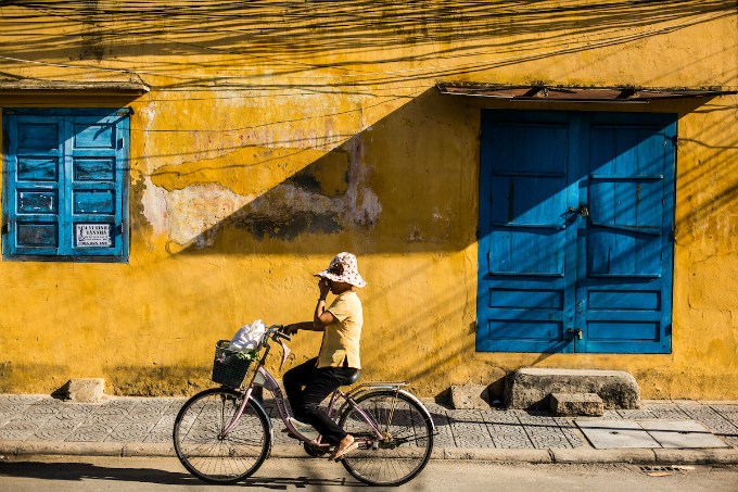A woman rides a bicycle past a typical yellow house of Hoi An. Photo by Christian Berg