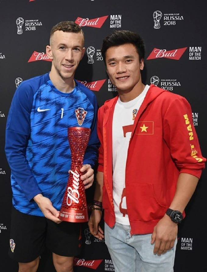 Vietnamese goalkeeper Bui Tien Dung (R) hands the Man of the match award to Croatian player Ivan Perisic.