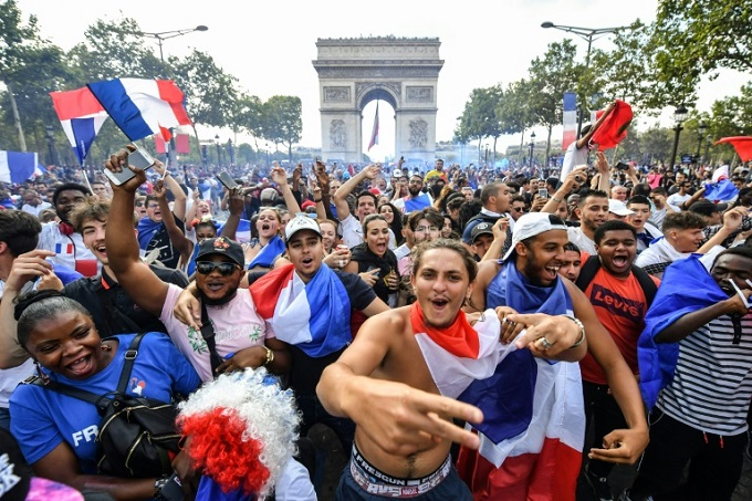 Massive crowds gathered on the Champs Elysees in Paris to celebrate. Photo by AFP