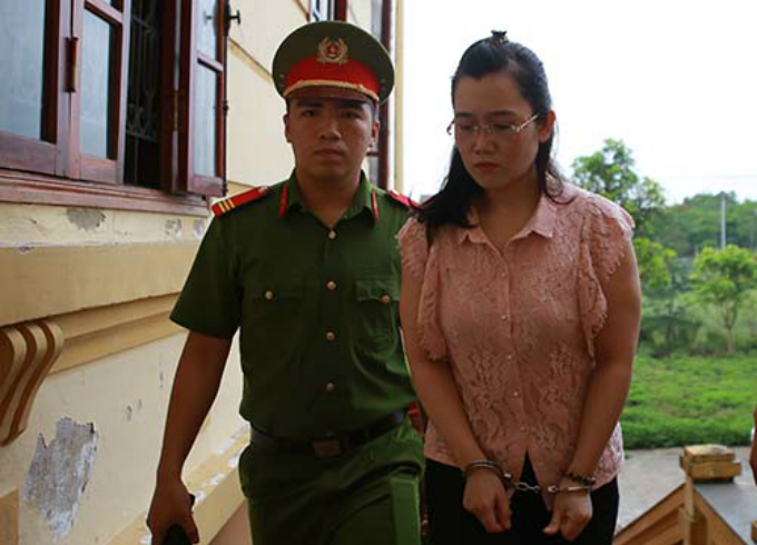 A police officer leads Nguyen Thi Lam (R) to court in Nghe An Province on Monday. Photo by VnExpress/Nguyen Hai