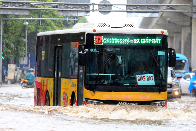 A bus rushes through the water in Quang Trung Road.