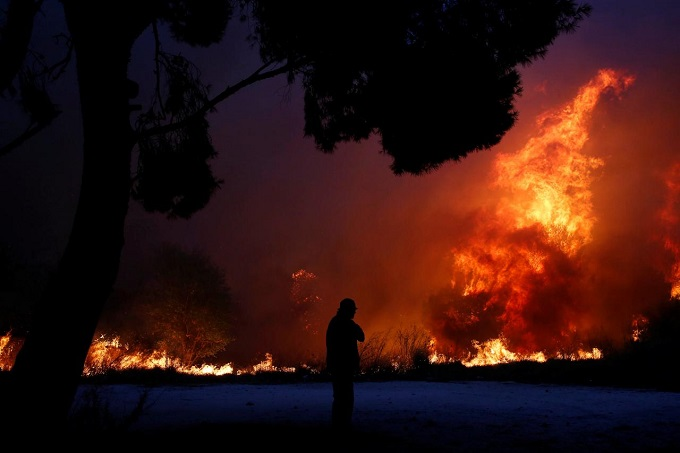 A man looks at the flames as a wildfire burns in the town of Rafina, near Athens, Greece, July 23, 2018. Photo by Reuters/Costas Baltas