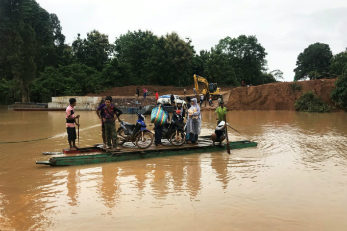 Makeshift ferries have been used to cross swollen rivers in the flash flood zone in southern Laos
