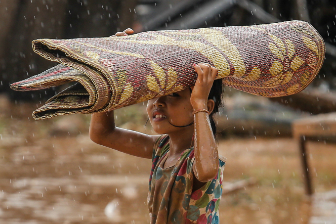 A little girl walks in the rain with a mat she picked up when water levels receded on Thursday.