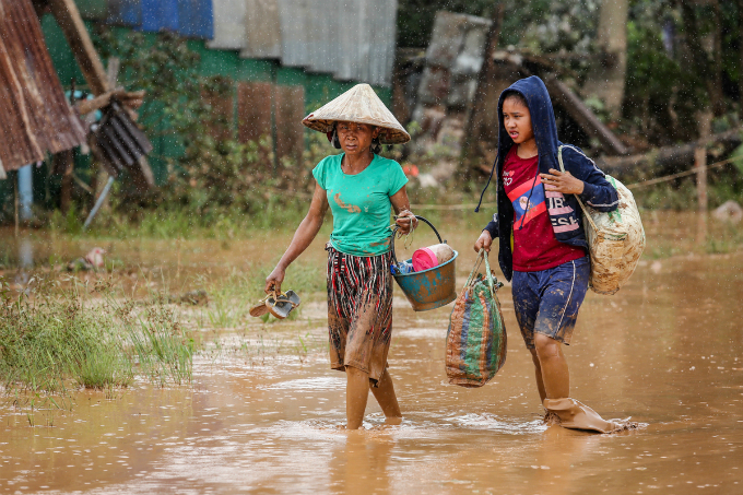 Two women take their belongings and move to a shelter. According to Laos officials, the dam collapse had affected the lives of 6,000 people in six villages, with more than 3,000 residents losing their homes.