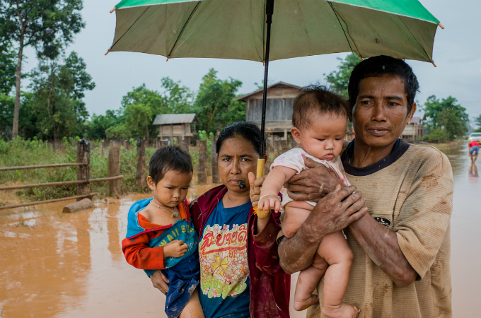 A couple wade through a street with their children. Many households have to move to safe shelters for fear of heavy rain and disease epidemics.
