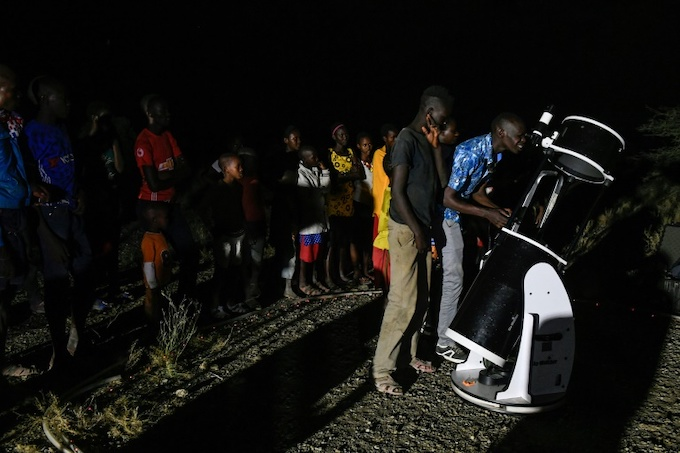 Young people watched the eclipse through a telescope beside Lake Magadi in Kenya. Photo by AFP