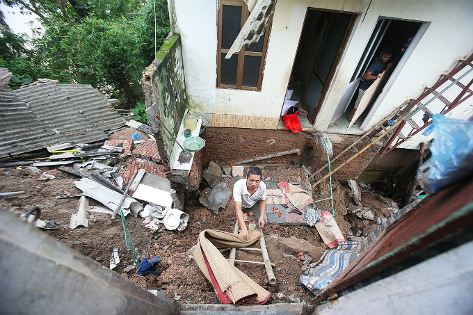 Some residents use bamboo ladder to climb down their old house which was sank two meters deep.