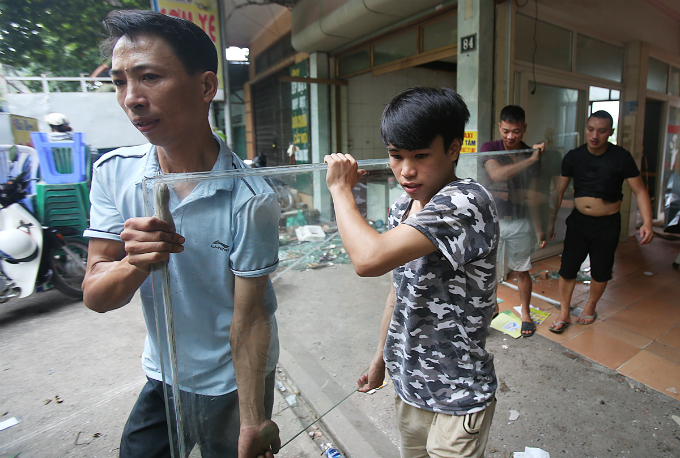 Some people dismantle the remaining glasses of a house on Cu Chinh Lan Street. Residents in the eroded area are racing against time for clearing away everything as many houses have been alerted to be pulled down.