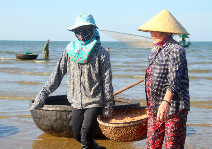 Villagers carry a basket full of krill.