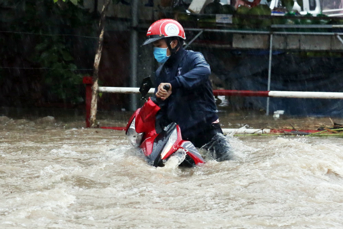 A man drives his motorbikes amid eddy water currents. Local residents blamed the encroaching construction on a stream through the area, resulting in the narrowed water flows. Therefore, when it rained cats and dogs, waters from the upstream spill onto the road and cause flooding.