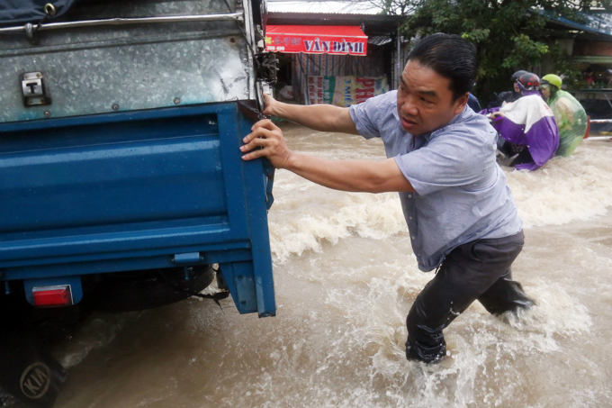 A truck driver walks his car on his own through the inundated water after his vehicles engines died due to rainwater.