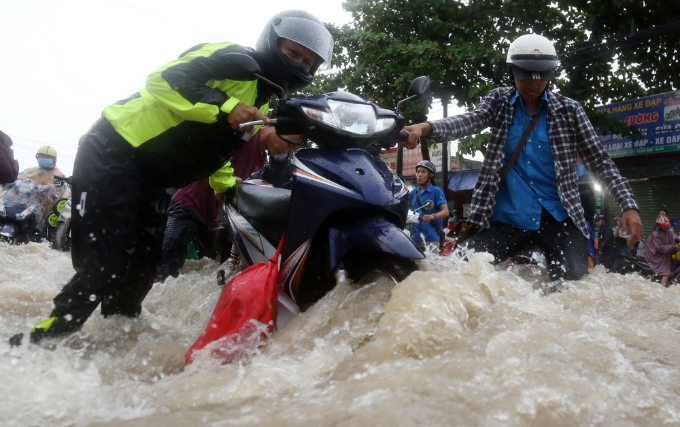 Some young men were willing to help tumbling motorists, especially women walk their motorbikes through the flooded water.