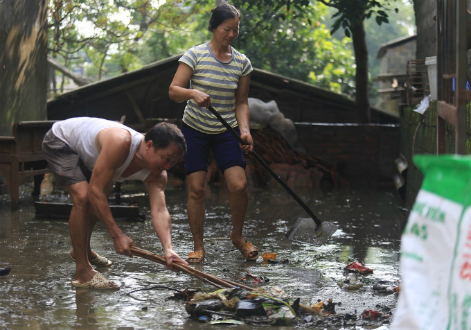 People push up trash to a drain so that sanitation workers come to collect. Garbage has been flowing to their house as the high water levels had brought them from dumpsites to there.