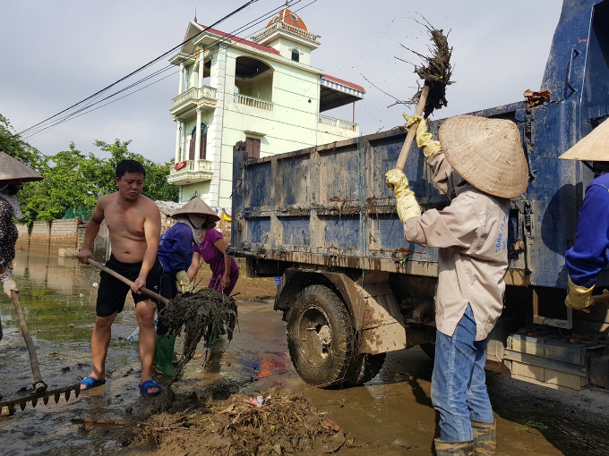 On Wednesday morning, locals and trash collectors cleared away muds on main roads leading to Nam Phuong Tien Commune.