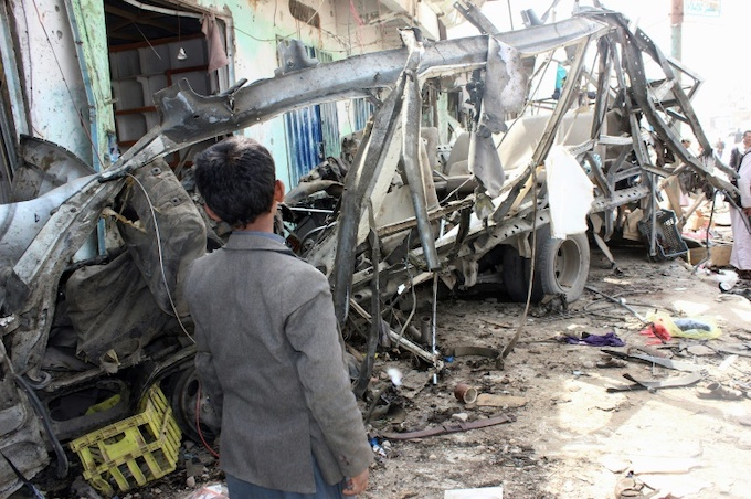 A Yemeni child stands next to the destroyed bus. Photo by AFP