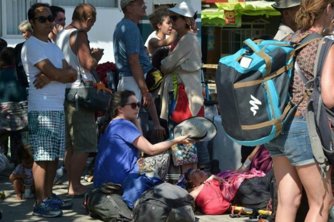 An injured Italian tourist (centre R) is shaded by another as they wait for an ambulance after locals and tourists were evacuated from the Gili islands north of Lombok.