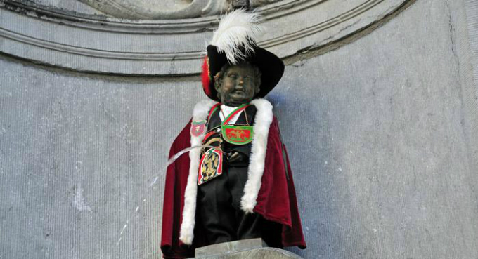 So small and yet so famous  and also so variable too! Manneken Pis is only 61 centimeters tall and yet a landmark of Brussels. The urinating bronze boy is naked but often costumed: Here he wears the regalia of the Order of St. Michael the Knight. He has about 1,000 outfits  each one with an open fly.