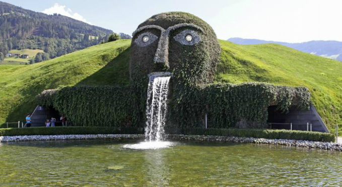 It is one of Austrias most popular sights: the giant in Wattens near  Innsbruck, a fountain and also a museum for crystal works of art.  Created by multimedia artist André Heller, it is inspired by the story  of a giant who set out to experience the world with all its treasures.  He retired in Wattens and has been watching over his chambers of  curiosities ever since.