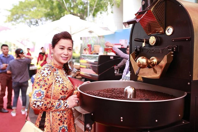 Le Hoang Diep Thao stands next to a coffee grinder at a King Coffee launch event. Photo courtesy of Le Hoang Diep Thaos official Facebook fanpage.