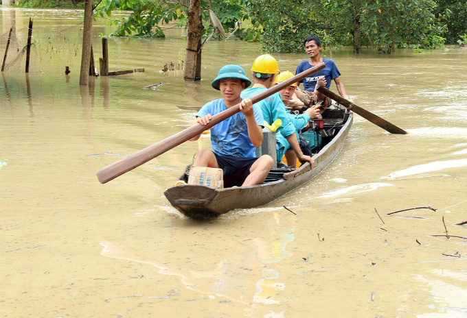 Local residents in Nghe An row a boat to wade through the flooded area triggered by heavy rains.
