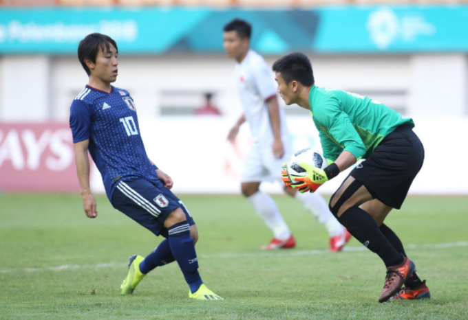 Vietnams goalkeeper Bui Tien Dung saves a shot from Japan.