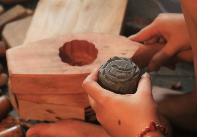 To test the quality of the mold, the craftsman makes a clay mooncake and places it into the mold to see if the measurement and decorative designs on top and side of the cake come out correct.