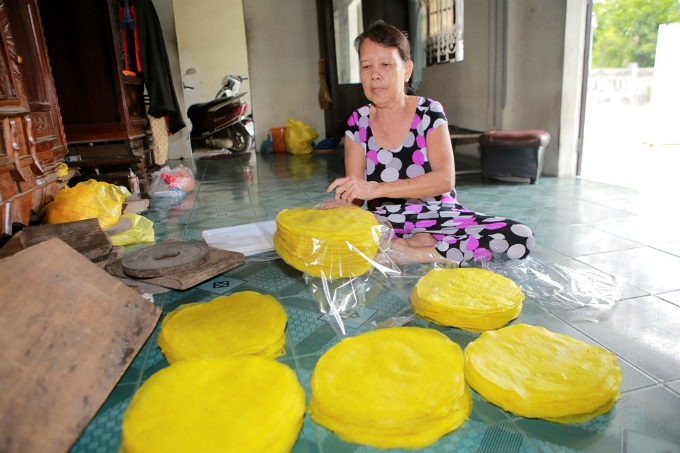 A woman stacks up the rice paper before packaging them. About 20 people in the village live off by this job.