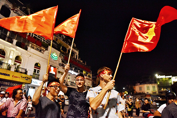 Foreign tourists join the waving flag in Hanoi. Photo by Giang Huy