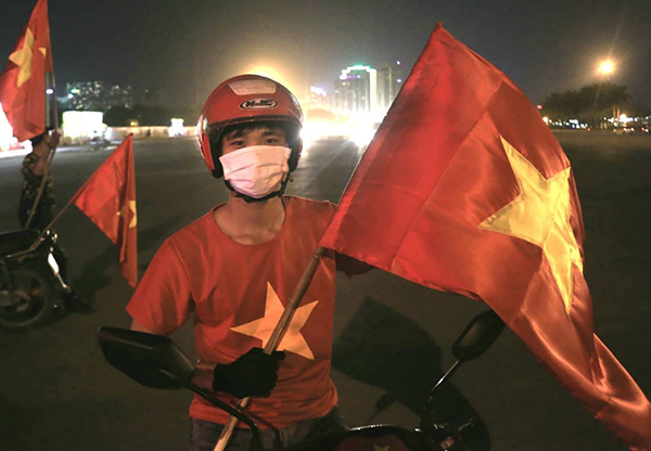 9:45 pm - Right after the game, Mai Van The, a student went out the street with a big Vietnam flag in his hands, ready to join the cheering crowd. Photo by Gia Chinh