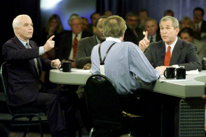 Republican presidential candidates John McCain and George W. Bush make points to moderator Larry King as Alan Keyes (partially obscured) looks on during a televised CNN Republican presidential debate, February 2000. Photo by Reuters/Files