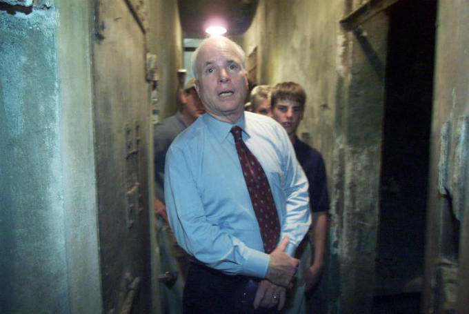 John McCain steps down a dark corridor separating jail cells with his son Jack during a tour of the infamous Hanoi Hilton where he spent time as a prisoner of war. During the 2005 visit McCain said he could not forgive the jailers who mistreated and killed his comrades. Photo by Reuters/Jason Reed