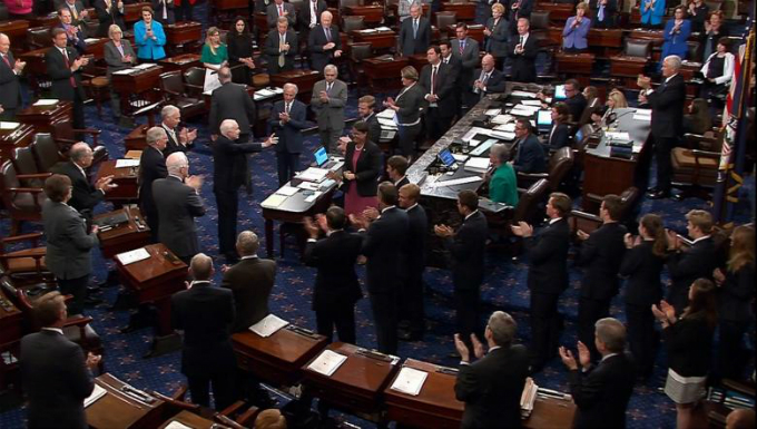 John McCain acknowledging applause as he arrives on the floor of the Senate after returning to Washington for a vote on healthcare reform, July 2017. SENATE TV/Via Reuters