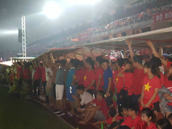 Vietnamese fans shield themselves from the rain as they watch the game live on a 150-square-meter screen at Lach Tray Stadium in Hai Phong.