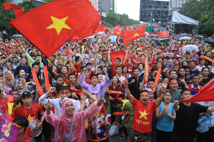 Fans react to Vietnams goal as they watch the game under the rain in Saigon. Photo by Huu Khoa