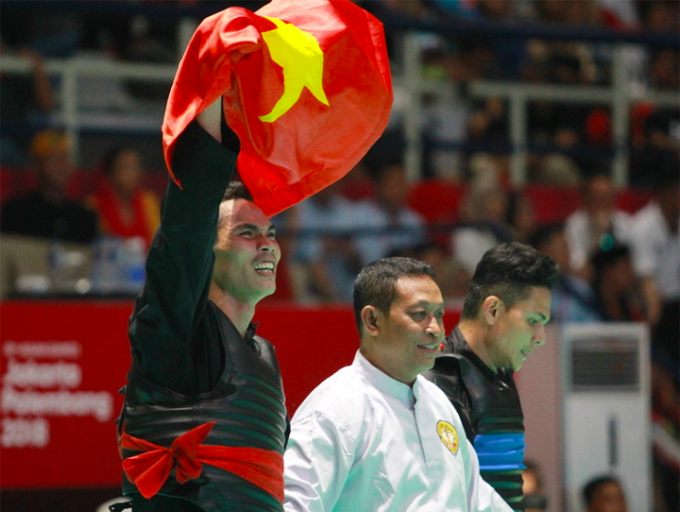 Tran Dinh Nam raises the national flag after winning a gold medal for Vietnam in Pencak Silat at ASIAD 2018. Photo by VnExpress/Xuan Binh