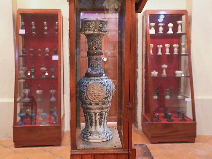 A large ceramic lampstand, nearly 1m tall, made during the Le Dynasty period, is displayed in its own cabinet.