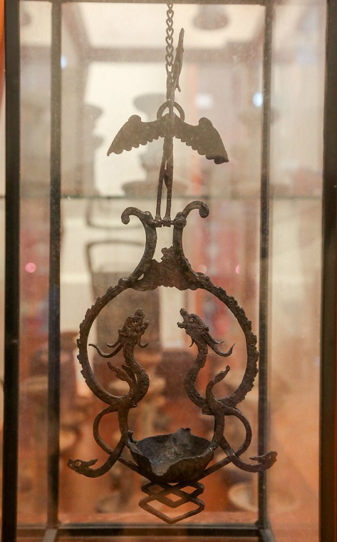 An iron lamp made by artists in Hue during the 19th century. It features the images of a dragon and a phoenix