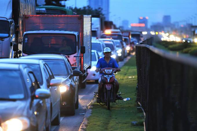 Vehicles on a road leading to Thanh Tri Bridge in Long Bien District in the capital city could only move at a snails pace. A motorcylist shifted to the roads sidewalk to keep moving.