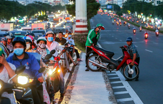 The gridlock stretched along the entire 3-km (1 mile) stretch from Binh Loi Bridge to the intersection of Pham Van Dong and Phan Van Tri streets. I waited for half an hour but couldnt escape the jam, then canceled a customers booking, said a GrabBike driver who carried his motorbike over the median strip to find another way.