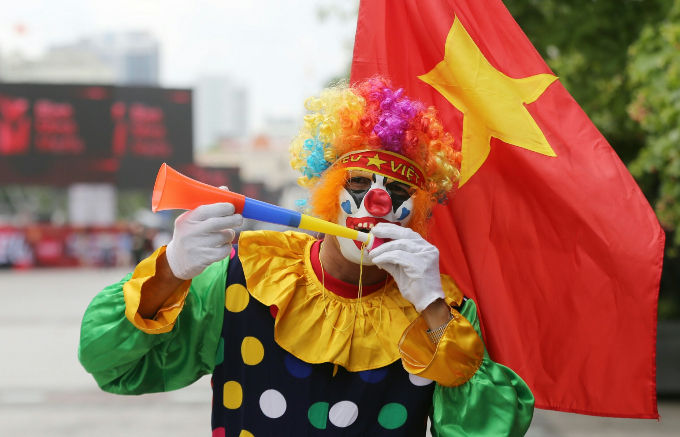 A fan puts on clown costume, ready to cheer for the national team, on Nguyen Hue walking street in District 1, HCMC. Photo by Quynh Tran